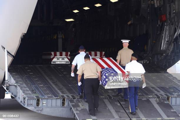 This picture taken on April 15 2018 shows US soldiers carrying a flagdraped coffin bearing the remains of a missing US soldier recovered by a team...