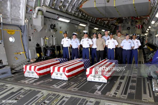 This picture taken on April 15 2018 shows US soldiers standing next to the three flagdraped coffins bearing the remains of missing soldiers recovered...