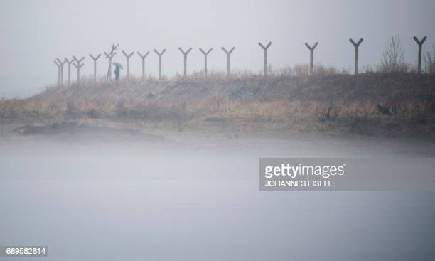 TOPSHOT This picture taken on April 17 2017 shows a North Korean man holding an umbrella while standing at a border fence amid fog next to the Yalu...