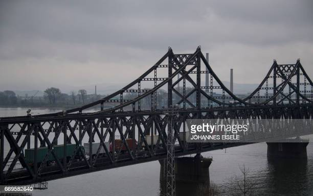 This picture taken on April 17 2017 shows trucks crossing the Friendship Bridge from the Chinese border city of Dandong to North Korea's Sinuiju over...