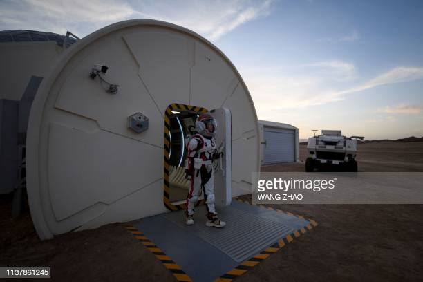 "This picture taken on April 17, 2019 shows a woman wearing a spacesuit walking out of ""Mars Base 1"", a C-Space Project, in the Gobi desert, some 40..."