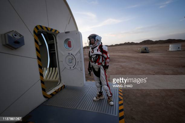 This picture taken on April 17 2019 shows a woman wearing a spacesuit walking out of Mars Base 1 a CSpace Project in the Gobi desert some 40...