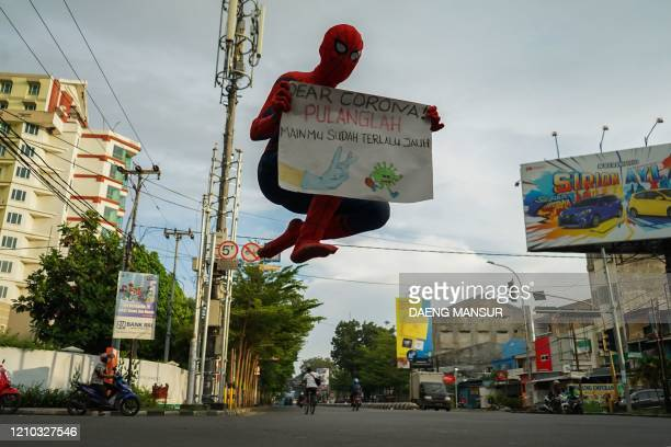 TOPSHOT This picture taken on April 17 2020 shows an Indonesian man in a superhero costume holding a placard reading dear corona go home you've gone...
