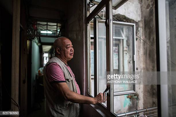 This picture taken on April 18 2016 shows Mr Chan looking out of the communal kitchen window near his 'cubicle' flat part of an apartment carved into...