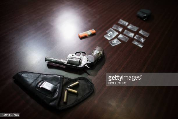 This picture taken on April 18 shows a gun and drug paraphernalia confiscated from an alleged drug dealer following his arrest by police after his...