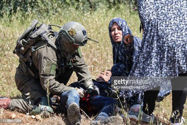 TOPSHOT This picture taken on April 18 shows an Israeli soldier performing first aid to 16yearold Palestinian Osama Ali alBadan after he was shot by...