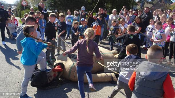 This picture taken on April 19 2019 shows children using sticks to beat an effigy of Judas on Good Friday April 19 2019 in the town of Pruchnik...