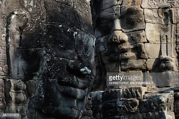 This picture taken on April 2 2014 shows stone faces of Mahayana Buddhist King Jayavarman VII at the Bayon temple part of the Angkor architectural...