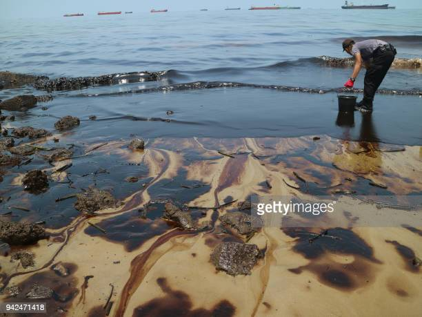 This picture taken on April 2 2018 shows an Indonesian policeman trying to clean Benua Patra beach after a nearby oil spill in Balikpapan An oil...