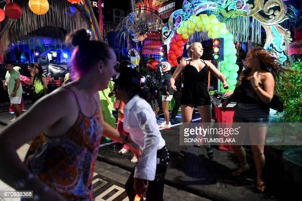 This picture taken on April 20 2017 shows foreign tourists dancing near Legian street in Kuta near Denpasar on Bali / AFP PHOTO / SONNY TUMBELAKA