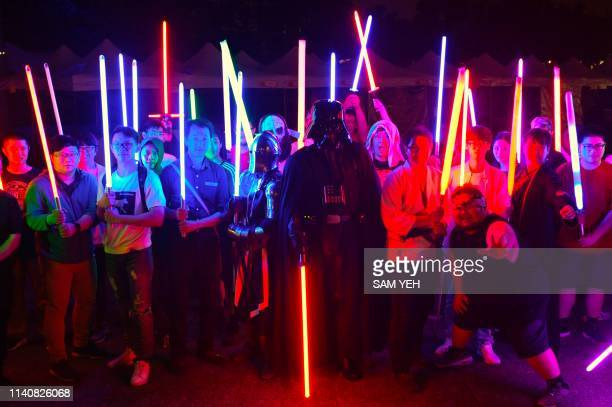 This picture taken on April 20 2019 shows fans posing for photographs with model lightsabers during an event to promote the upcoming unofficial Star...