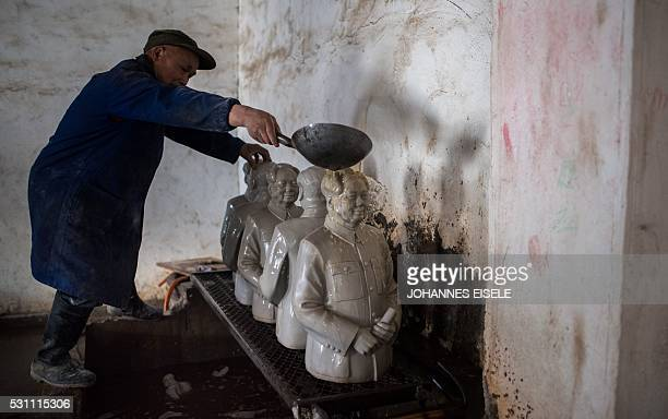 This picture taken on April 21 2016 in Shaoshan shows a worker pouring liquid over Mao statues in a small factory Shaoshan in central China's...