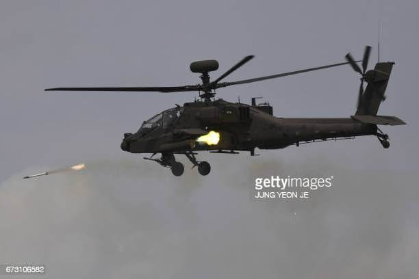 This picture taken on April 21 2017 shows a South Korean AH64E Apache helicopter firing rockets during a media day presentation of a joint live...