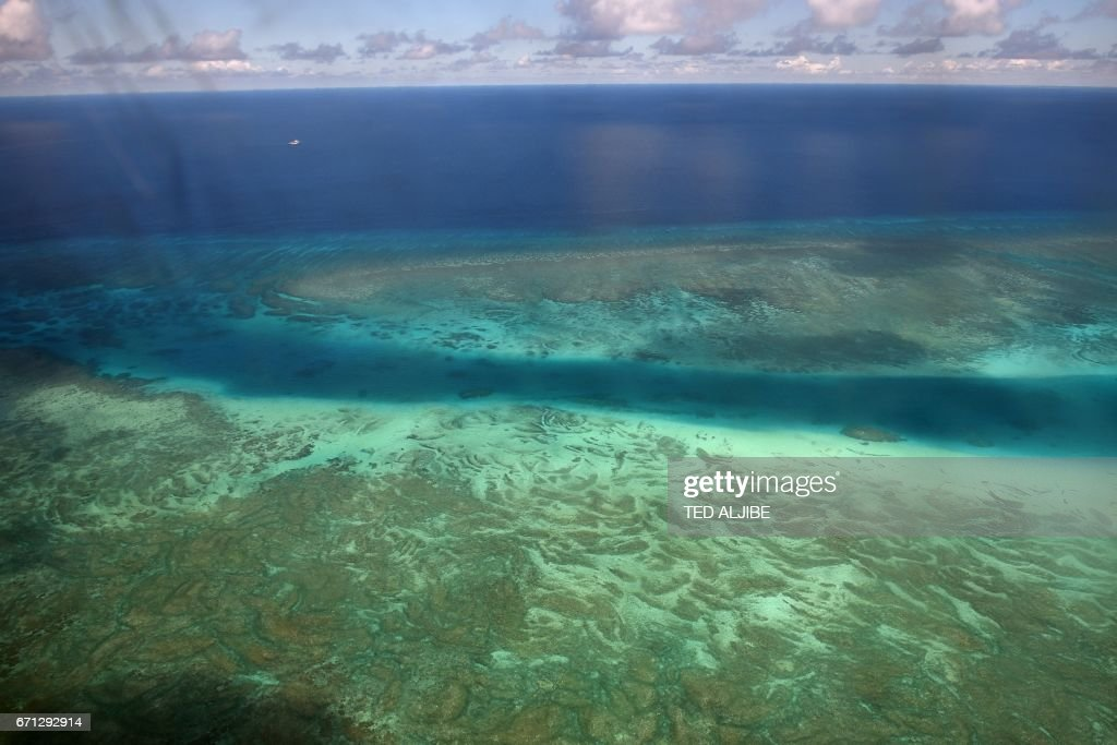 This picture taken on April 21, 2017 shows an aerial view of a reef near Thitu island in the disputed Spratly islands. Philippine Defence Secretary Delfin Lorenzana flew to a disputed South China Sea island on April 21, brushing off a challenge by the Chinese military while asserting Manila's territorial claim to the strategic region. / AFP PHOTO / Ted ALJIBE