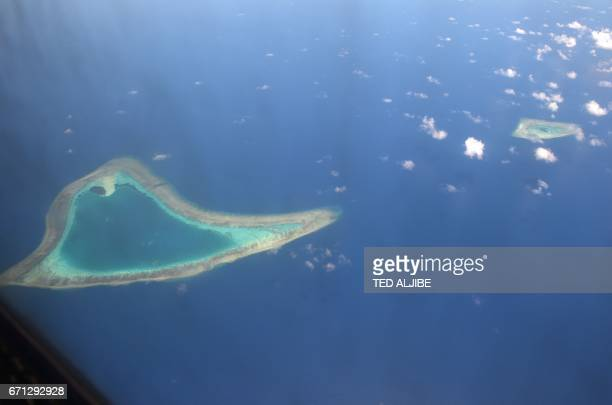 This picture taken on April 21 2017 shows an aerial view of reefs in the disputed Spratly islands Philippine Defence Secretary Delfin Lorenzana flew...