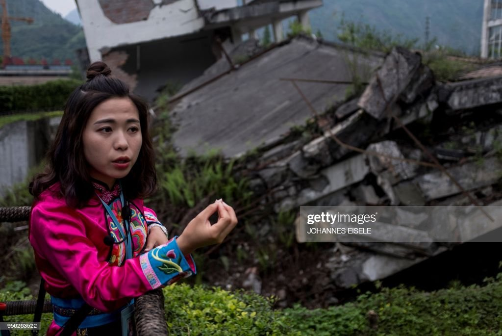 This picture taken on April 21, 2018 shows a 25-year-old guide, surnamed Ma, next to a memorial site in of the 2008 Sichuan earthquake in Yingxiu, near Beichuan in Sichuan province. - The city of Beichuan has been kept frozen in time since May 12, 2008, when a 7.9-magnitude earthquake killed some 87,000 people across Sichuan province. (Photo by Johannes EISELE / AFP) / TO GO WITH China-quake-tourism,FOCUS by Ben Dooley