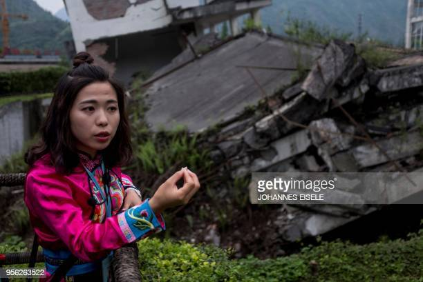 This picture taken on April 21 2018 shows a 25yearold guide surnamed Ma next to a memorial site in of the 2008 Sichuan earthquake in Yingxiu near...