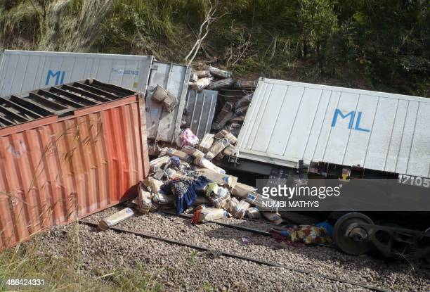 This picture taken on April 22, 2014 shows the body of a victim and derailed wagons after a train sped off the rails 65km north of Kamina, in the...