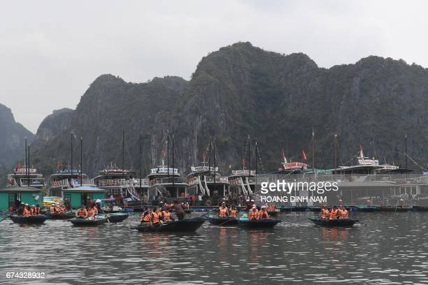 This picture taken on April 23 2017 shows bamboo boats transporting tourists from their motorised boats to tour caves in Halong Bay in the...