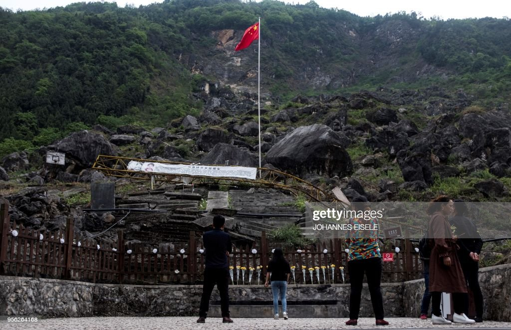 This picture taken on April 23, 2018 shows tourists looking at the site where the Beichuan Middle School which was buried by boulders during the 2008 Sichuan earthquake in Beichuan, Sichuan province. - The city of Beichuan has been kept frozen in time since May 12, 2008, when a 7.9-magnitude earthquake killed some 87,000 people across Sichuan province. (Photo by Johannes EISELE / AFP) / TO GO WITH China-quake-tourism,FOCUS by Ben Dooley