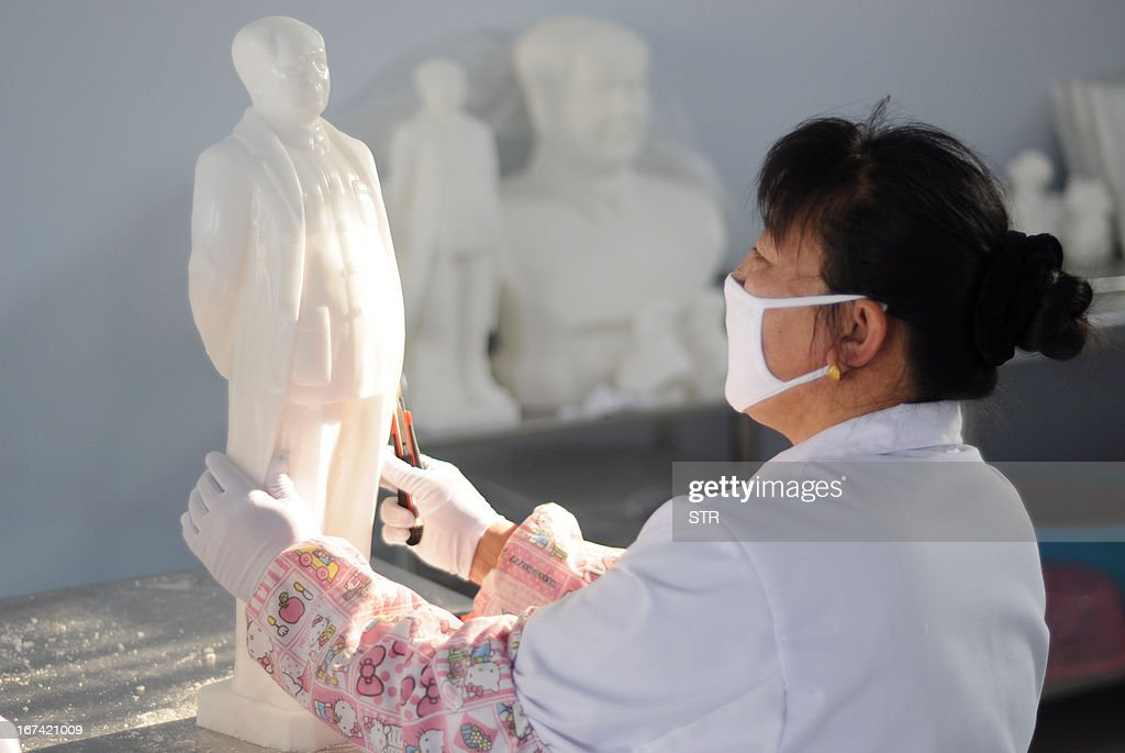 This picture taken on April 24, 2013 shows a worker caving a Chairman Mao sculpture with sea salt in Wudi county of Binzhou, east China's Shandong province. The county also developed sculptures of other famous people in China, such as Confucius. CHINA