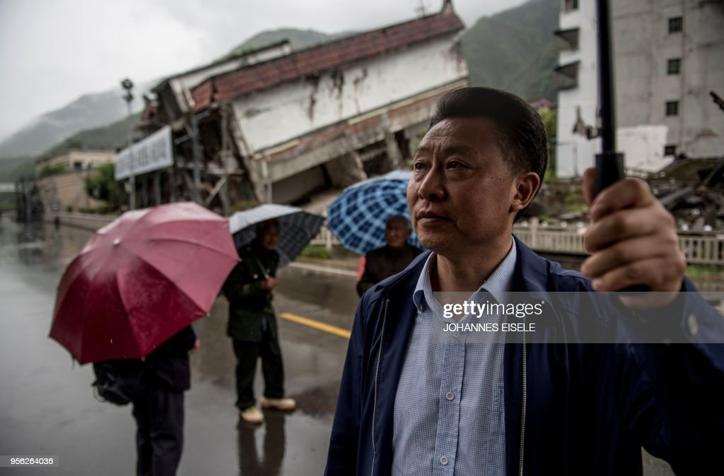 This picture taken on April 24, 2018 shows Chen Guoxing posing for a picture in front of houses destroyed by the 2008 Sichuan earthquake in Beichuan, Sichuan province. - The city of Beichuan has been kept frozen in time since May 12, 2008, when a 7.9-magnitude earthquake killed some 87,000 people across Sichuan province. (Photo by Johannes EISELE / AFP) / TO GO WITH China-quake-tourism,FOCUS by Ben Dooley