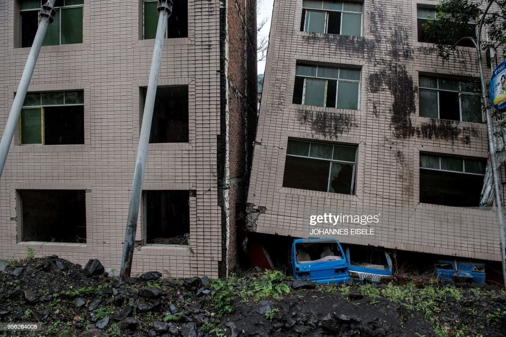 This picture taken on April 24, 2018 shows houses destroyed by the 2008 Sichuan earthquake in Beichuan, Sichuan province. - The city of Beichuan has been kept frozen in time since May 12, 2008, when a 7.9-magnitude earthquake killed some 87,000 people across Sichuan province. (Photo by Johannes EISELE / AFP) / TO GO WITH China-quake-tourism,FOCUS by Ben Dooley