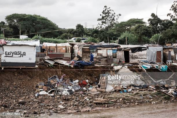 This picture taken on April 24 2019 shows a man trying to rebuild his destroyed shack at the Quarry road informal settlement after torrential rains...