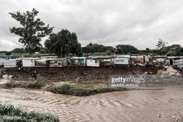 This picture taken on April 24 2019 shows people trying to rebuild their destroyed shacks at the Quarry road informal settlement after torrential...