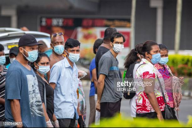 This picture taken on April 24, 2021 shows residents wearing face masks waiting to cross the main road in the Fijian capital Suva ahead of an...
