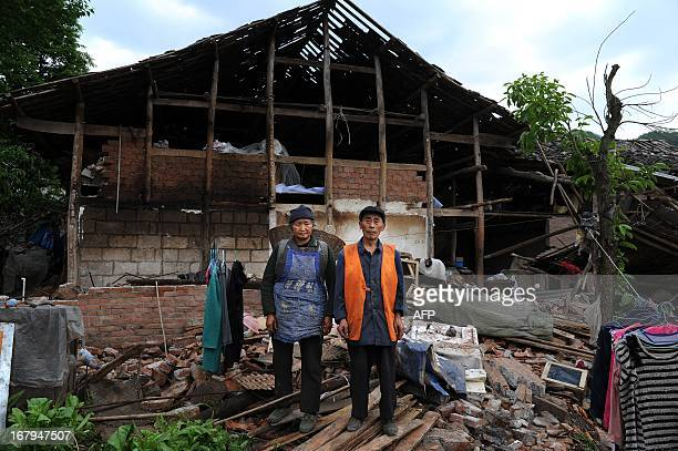 This picture taken on April 25 2013 shows He Fupin and his wife standing in front of their damaged house in Longmen township of Lushan county an area...