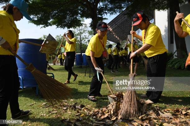 This picture taken on April 25 2019 shows Thailand Post Company Ltd employees sweeping the lawn outside their offices in honour of Thailand's King...