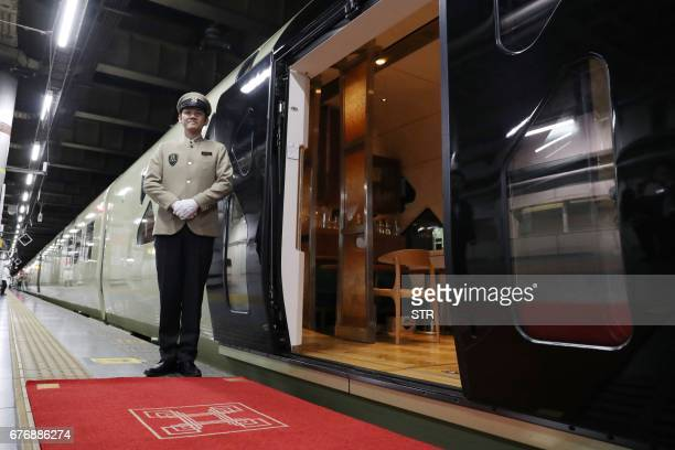 This picture taken on April 26 2017 shows a crew member standing next to the Train Suite ShikiShima operated by East Japan Railway at Ueno Station in...