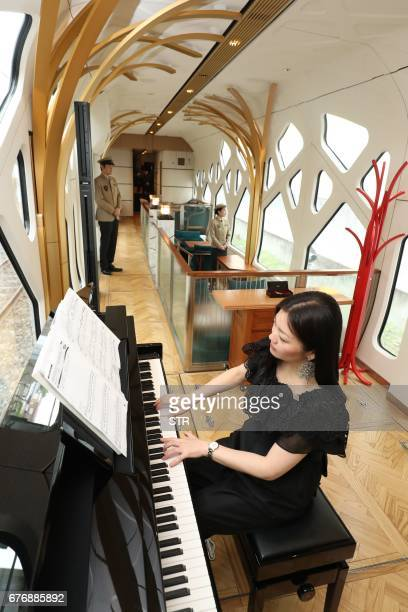 This picture taken on April 26 2017 shows a woman playing the piano in the lounge car of the Train Suite ShikiShima operated by East Japan Railway in...