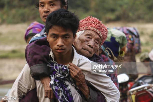 TOPSHOT This picture taken on April 26 2018 shows displaced Kachin residents crossing Malikha river on a ferry to escape the fighting in Injanyan...