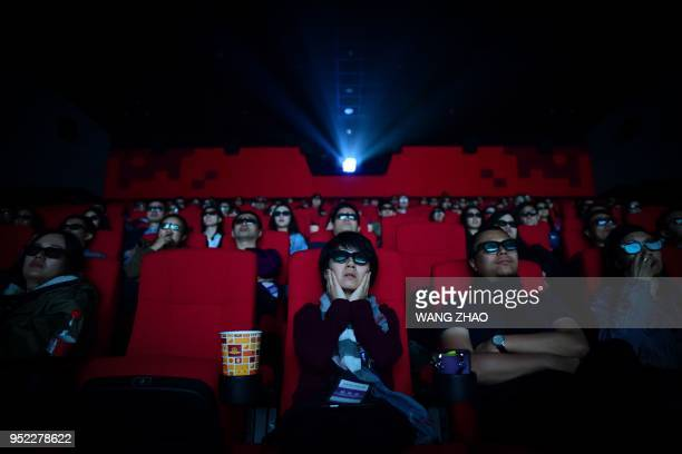 This picture taken on April 27 2018 shows people watching a movie at a cinema in Wanda Group's Oriental Movie Metropolis in Qingdao China's Shandong...