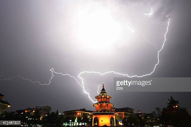 This picture taken on April 28 2015 shows lightning brightening the sky over a pagoda in Yangzhou east China's Jiangsu province CHINA OUT AFP PHOTO