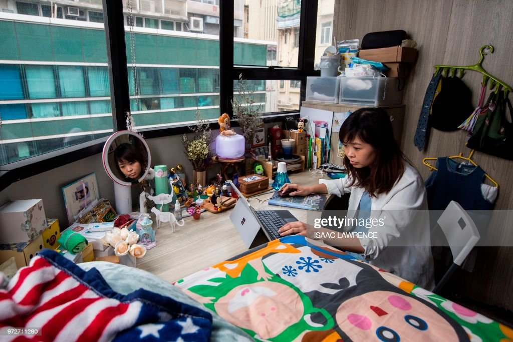 This picture taken on April 28, 2018 shows Jezz Ng siting at her desk where she rents a small living space in a co-sharing building in the Mong Kok district of Hong Kong. - As housing prices spiral in Hong Kong, young professionals are living in ever-shrinking spaces, with box-like 'nano-flats' and co-shares touted as fashionable solutions. (Photo by ISAAC LAWRENCE / AFP)