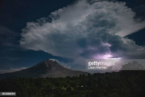 TOPSHOT This picture taken on April 28 2018 shows lighting and thunder over Mount Sinabung volcano in Karo Sinabung roared back to life in 2010 for...