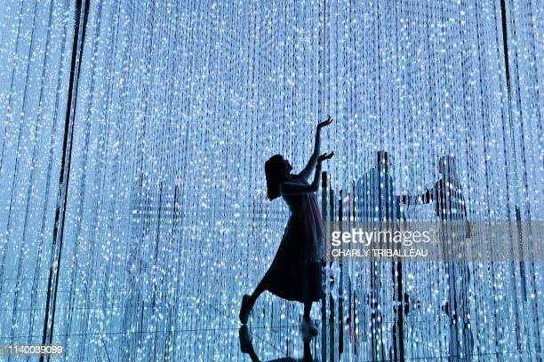 This picture taken on April 28 2019 shows a woman enjoying her visit at the team lab borderless museum of Tokyo Collective teamLab known...