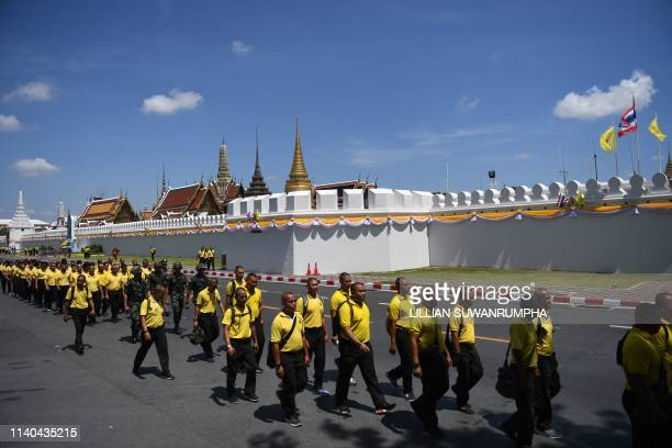 This picture taken on April 28 2019 shows volunteers walking in front of the Grand Palace before a rehearsal for the royal coronation of Thailands...