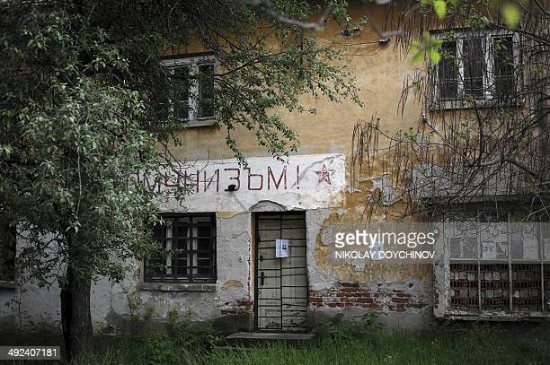 This picture taken on April 29 2014 shows a sign reading in Bulgarian Peace work and communism on a former municipality building in the village of...