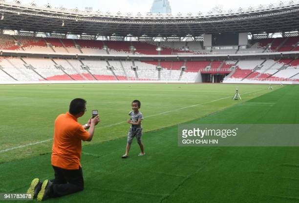 This picture taken on April 3 2018 shows an Indonesian man taking photo of his son at the main stadium Gelora Bung Karno for the Asian Games in...