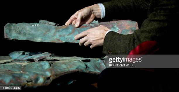 This picture taken on April 3 2019 shows copper plates from a ship wreck from 1536 that was discovered during the storage of the containers that were...