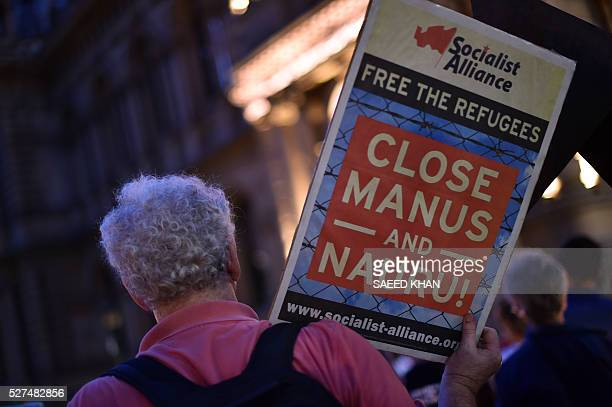 This picture taken on April 30 2016 shows a participant holding a placard during a vigil in Sydney for an Iranian refugee who died after setting...