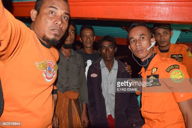 This picture taken on April 5 2018 shows Indonesian rescuers flanking two men part of a group of five Rohingya Muslims rescued by Indonesian...