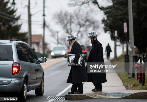 This picture taken on April 5 2019 shows shows a two Jewish men hitchhiking in a Jewish neighborhood of Monsey in Rockland County New York A measles...