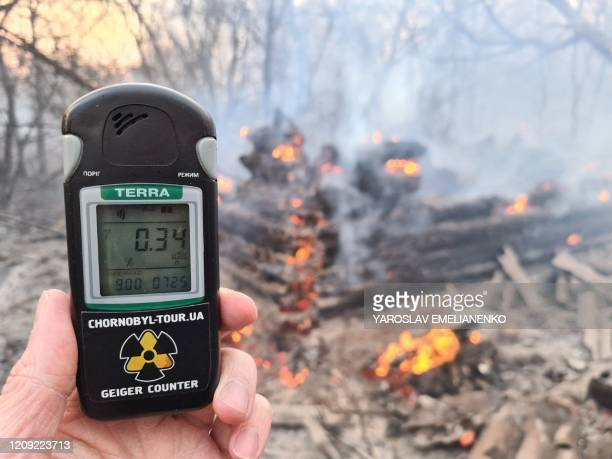 This picture taken on April 5 shows a person holding a Geiger counter at the scene of a forest fire at a 30-kilometer Chernobyl exclusion zone, not...