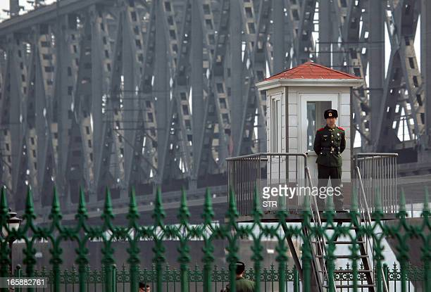 This picture taken on April 6 2013 shows a Chinese border guard standing on a look out post by the bridge that crosses the Yalu river to the North...