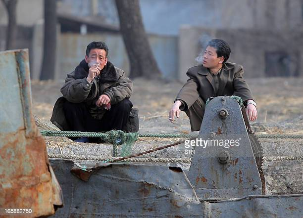 This picture taken on April 6 2013 shows two North Korean men resting by the docks along the Yalu river in the North Korean town of Sinuiju across...